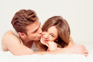 Happy young man in love kissing his girlfriend lying on the bed